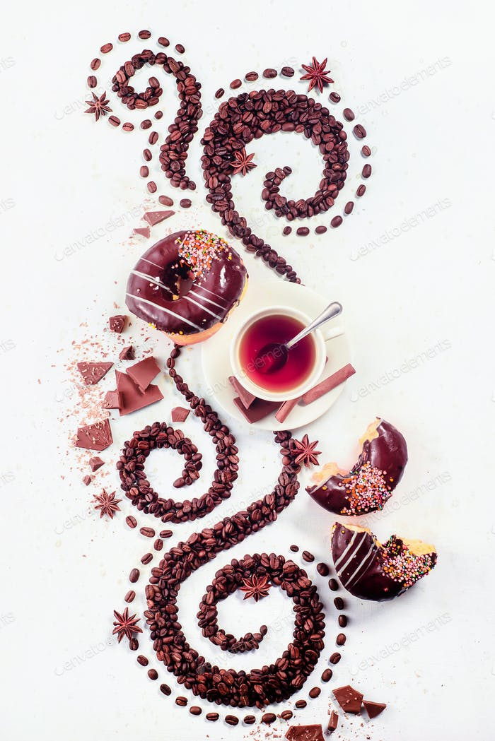 Coffee grains lying in the shape of a swirl with the cup, cinnamon, anise stars and donuts