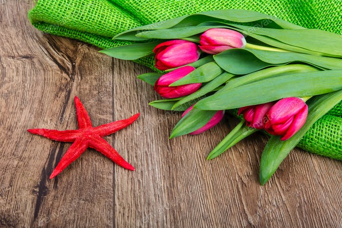 Starfish and tulips on a wooden table