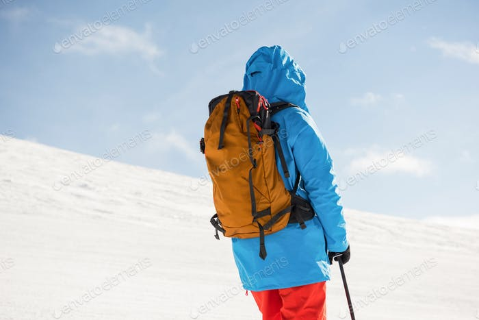 Skier standing with ski on snowy mountains