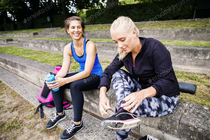 Smiling fit women sitting on steps at park