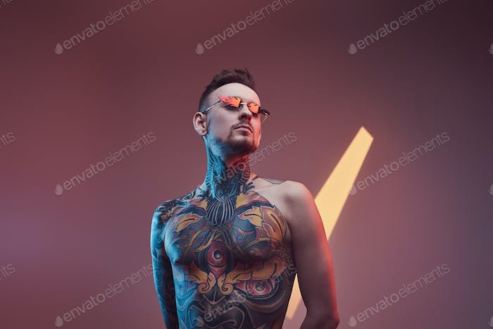 Brutal caucasian guy with tattooed body in colourful background