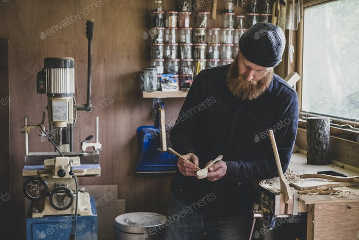 Bearded man wearing black beanie standing at workbench in workshop, examining piece of wood.