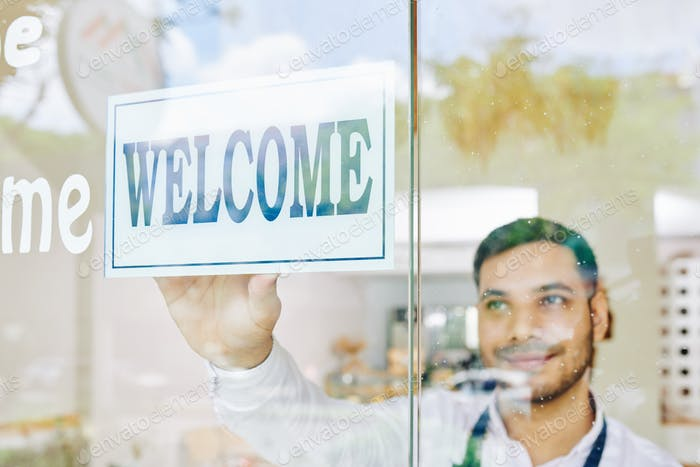 Shop owner sticking welcome sign