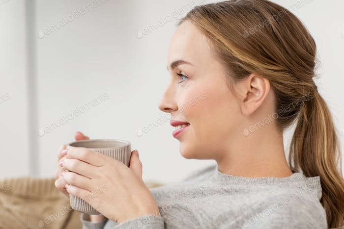 happy woman with cup or mug drinking at home