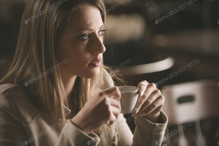 Woman having a coffee at the bar