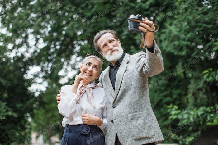 Senior family taking selfie on retro camera at park