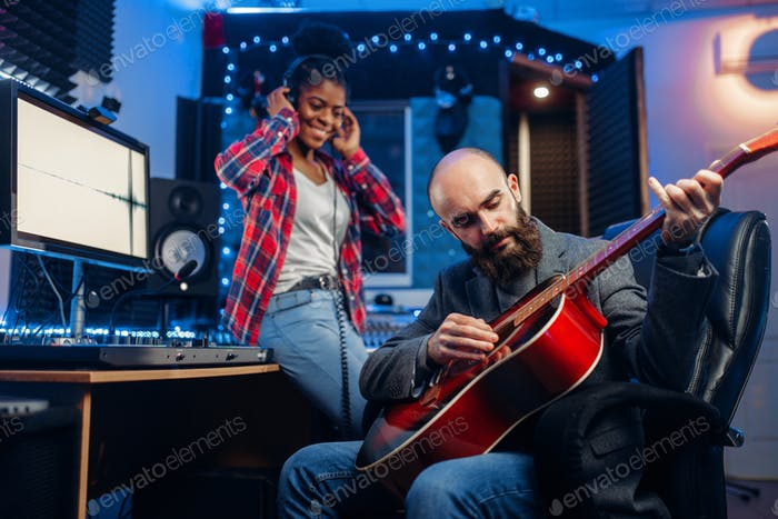 Male and female musicians in recording studio