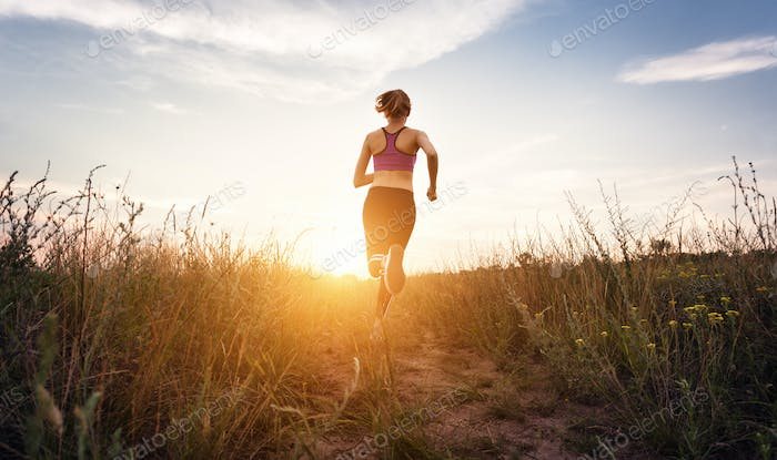 Young sporty girl running on a rural road at sunset