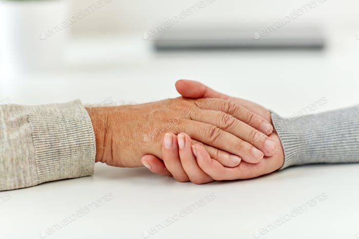 close up of old man and young woman holding hands