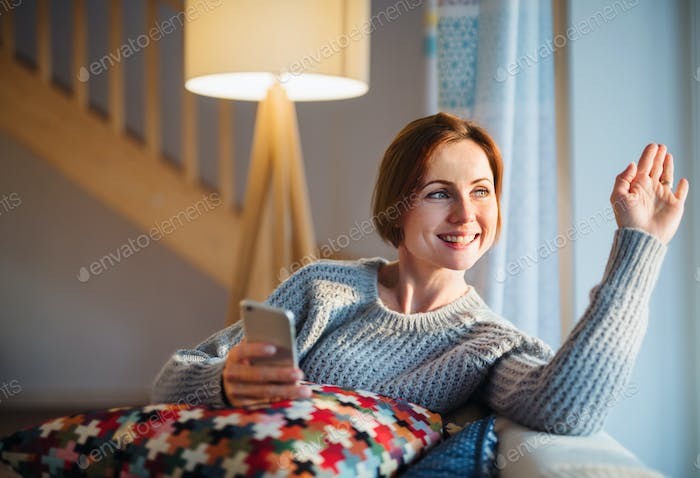 A young woman with smartphone sitting indoors on a sofa at home, waving.