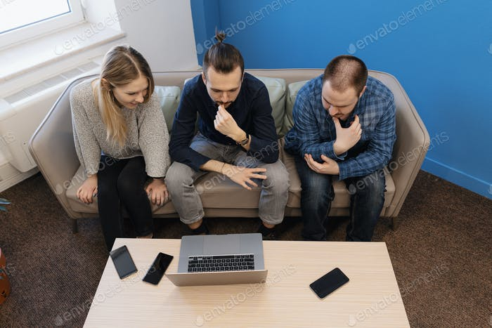 Team of three people working on laptop in the office on the sofa