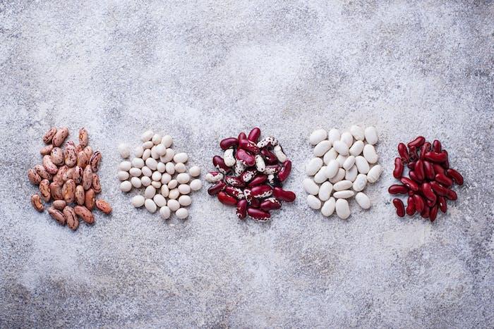 Assortment of various beans on light  background