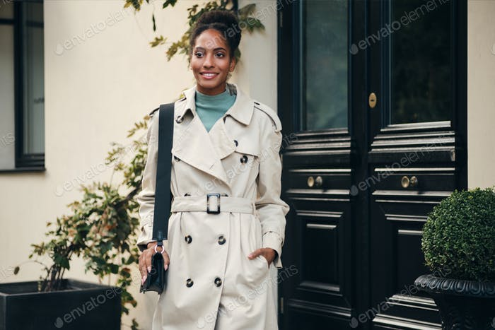 Attractive African American girl in stylish trench coat with little bag going out the building
