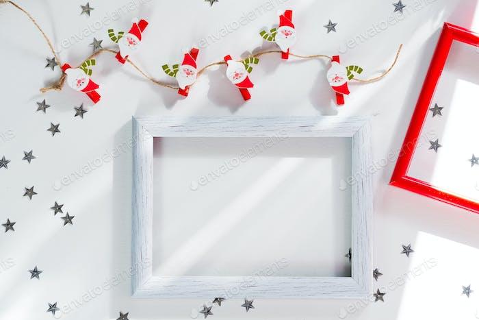 Fröhliche Weihnachten und Neujahr Rahmen-Mockup. Weihnachtsmann, silberner Stern und Bilderrahmen auf weiß