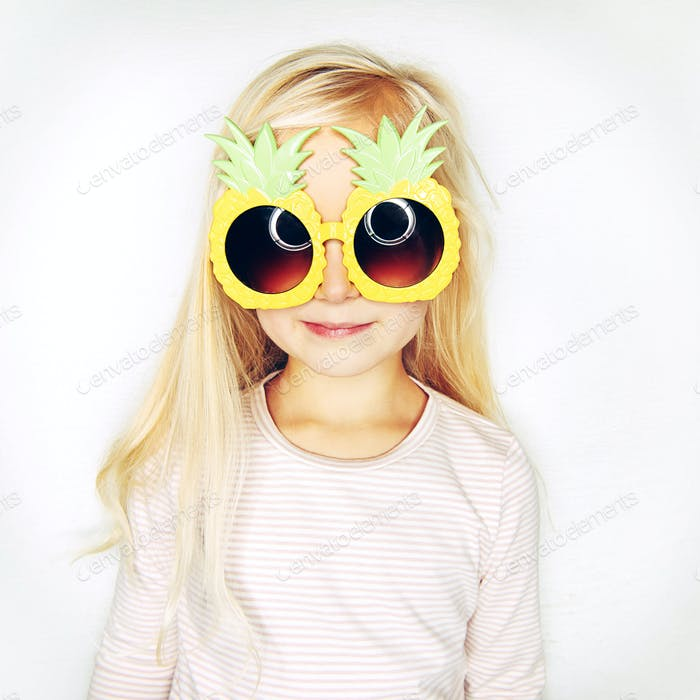 Little girl in pineapple sunglasses in studio