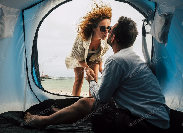 Love and kiss in free tent camping vacation for adult beautiful couple at the beach
