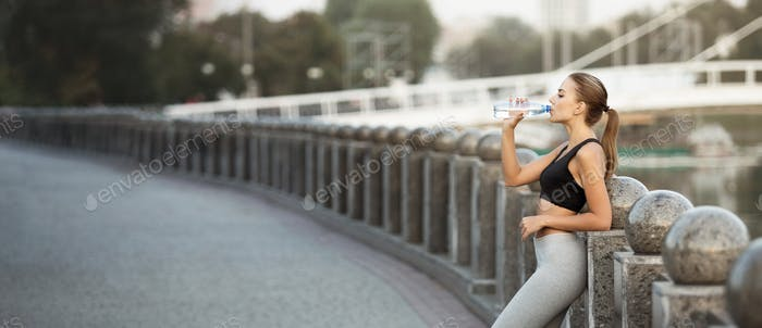 Sporty millennial woman drinking water after run practice on bridge