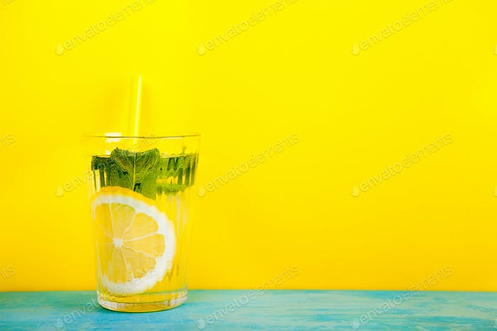 Glass with organic and fresh lemonade over yellow background