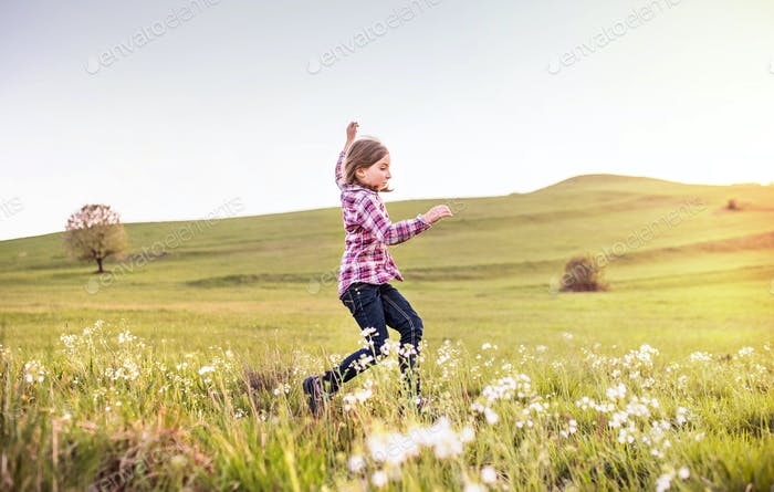 A small girl having fun outside in nature.