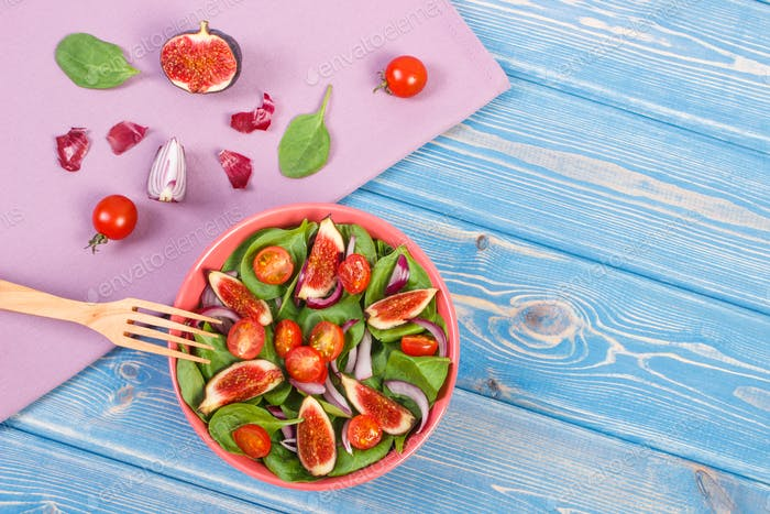 Fruit and vegetable salad with wooden fork, concept of healthy nutrition