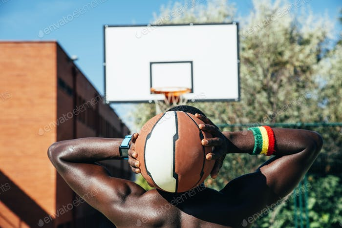 Male basketball player holding a ball.
