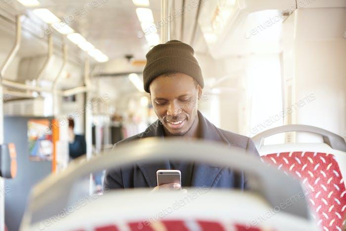 Привлекательный молодой афро-американец мужчина в стильной шляпе и пальто сидит в автобусе и обмен друзьями