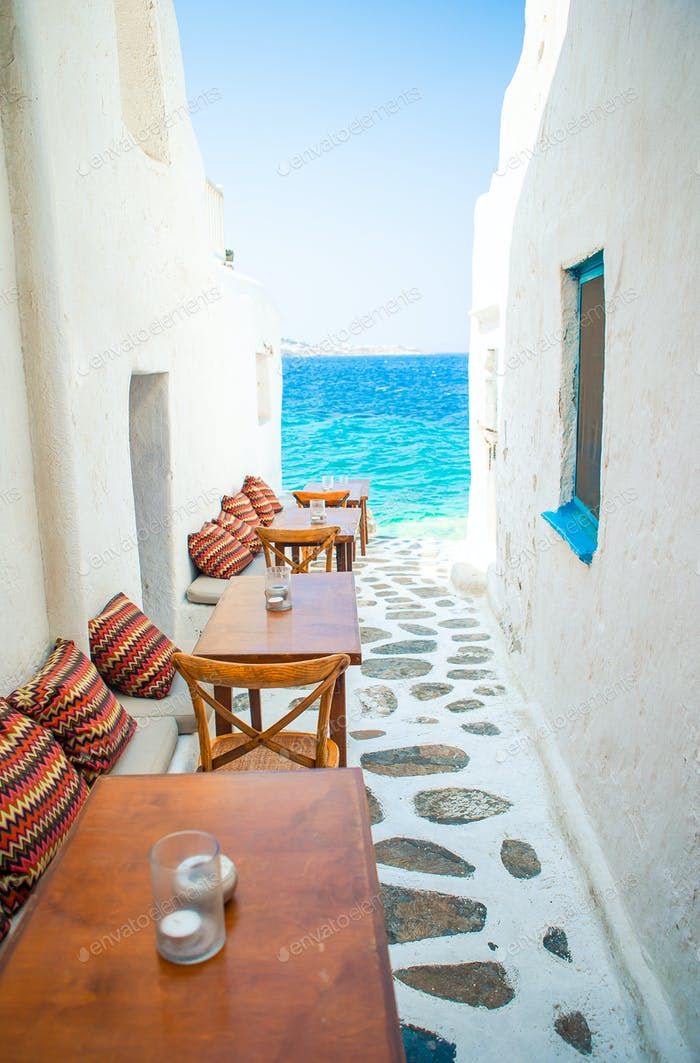Benches with pillows in a typical greek outdoor cafe in Mykonos with amazing sea view on Cyclades