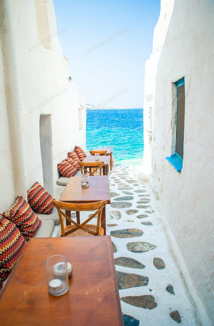 Bänke mit Kissen in einem typisch griechischen Outdoor-Café in Mykonos mit herrlichem Meerblick auf Kykladen