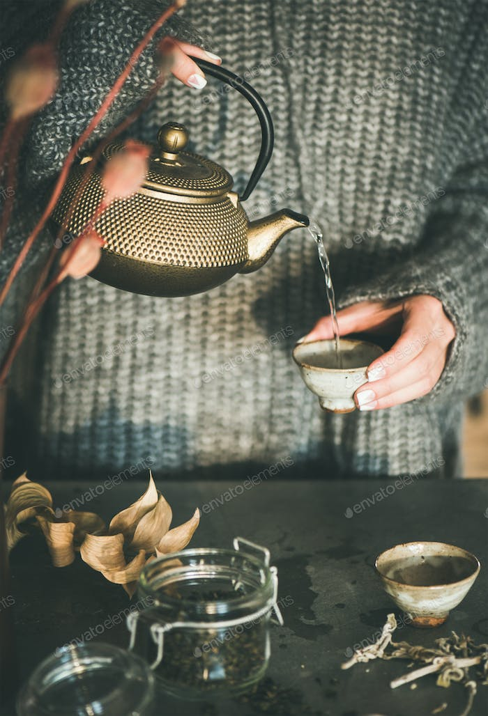 Woman pouring tea from golden teapot into cup