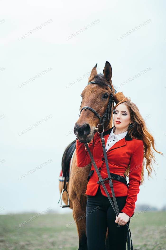 red-haired jockey girl in a red cardigan and black high boots with a horse