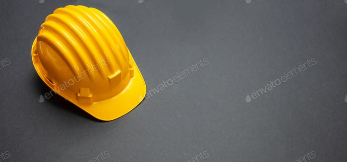 Construction project safety, Yellow hard hat on black color background, copy space