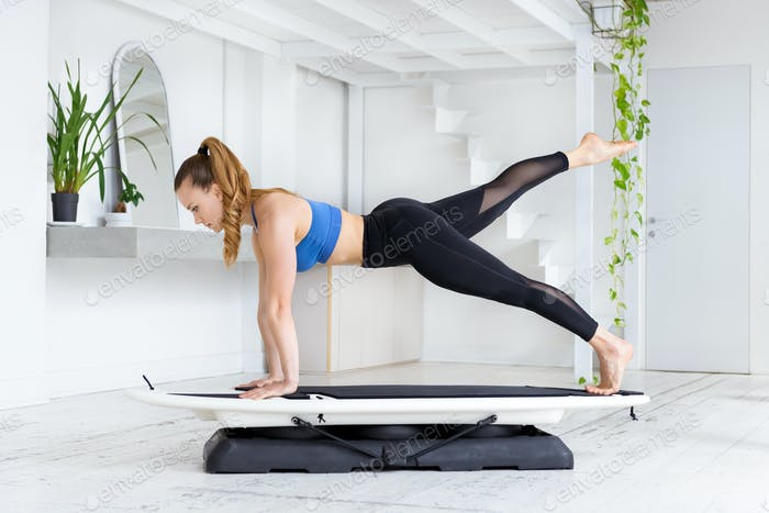 Woman doing a fit surf plank kick back