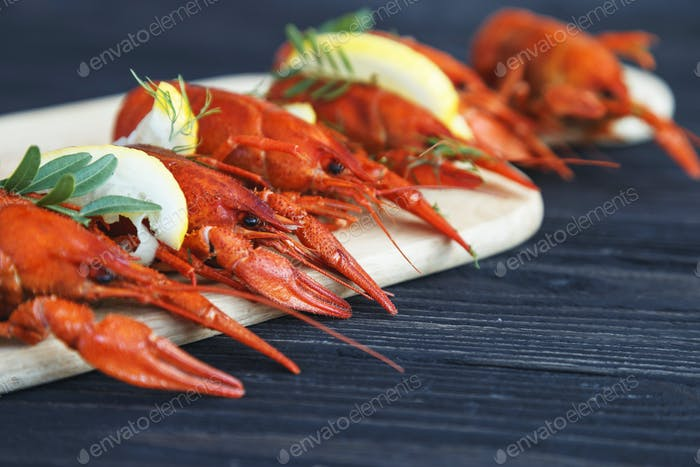 Close-up of boiled crawfish with lemon and herbs