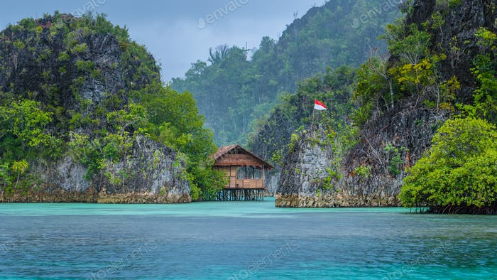Bamboo Hut between some Rocks under Rain in Bay with Indonesian Flag, Pianemo Islands, Raja Ampat