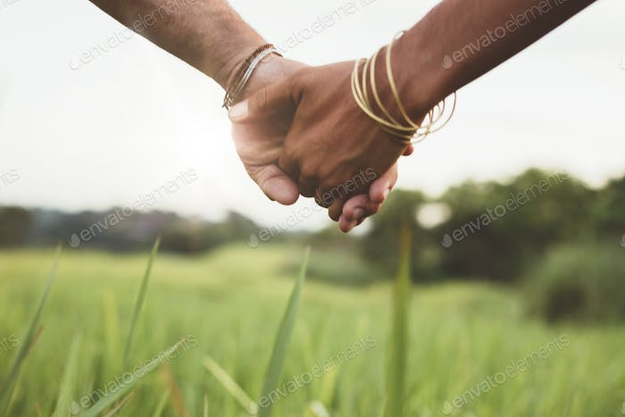 Young couple holding hands in the field