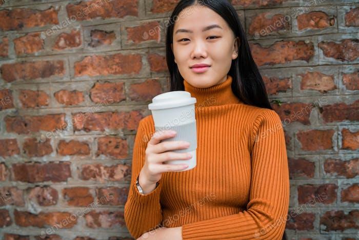 Asiatische Frau hält eine Tasse Kaffee.