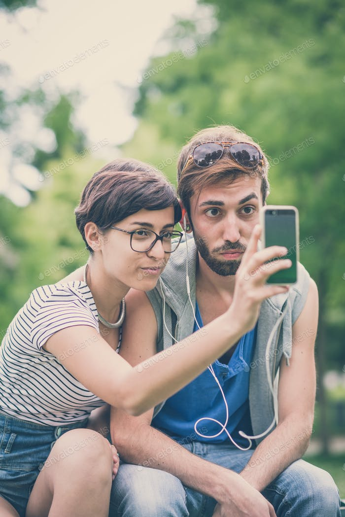 couple of friends young  man and woman using smartphone