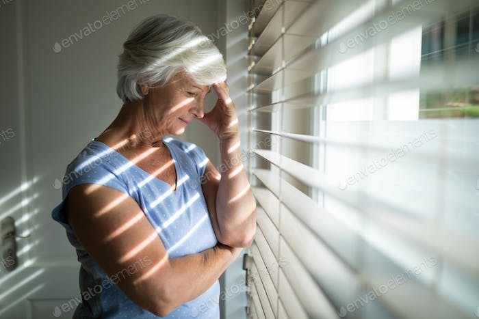 Tense senior woman standing near window in bedroom