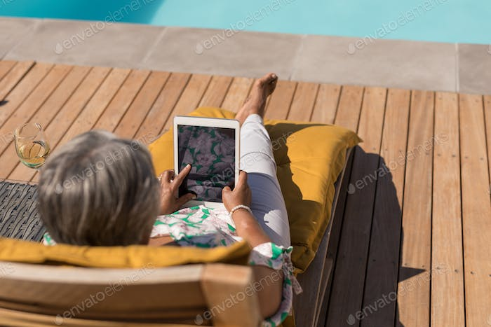 Active African American senior woman using digital tablet while relaxing on a lounger chair