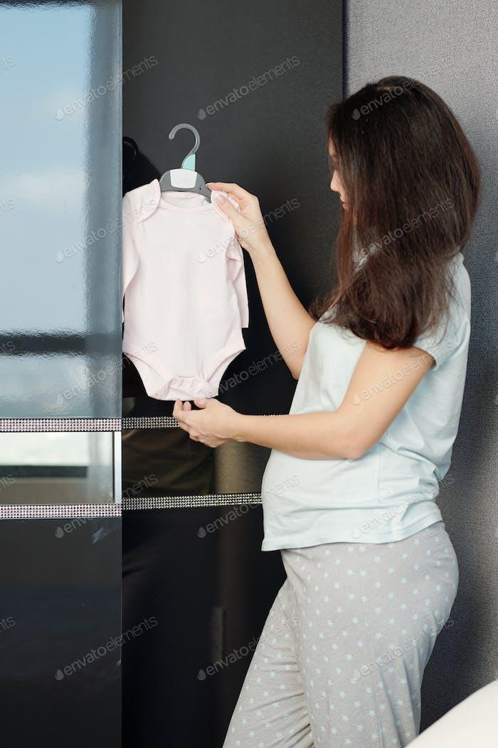 Pregnant woman holding kid onsie