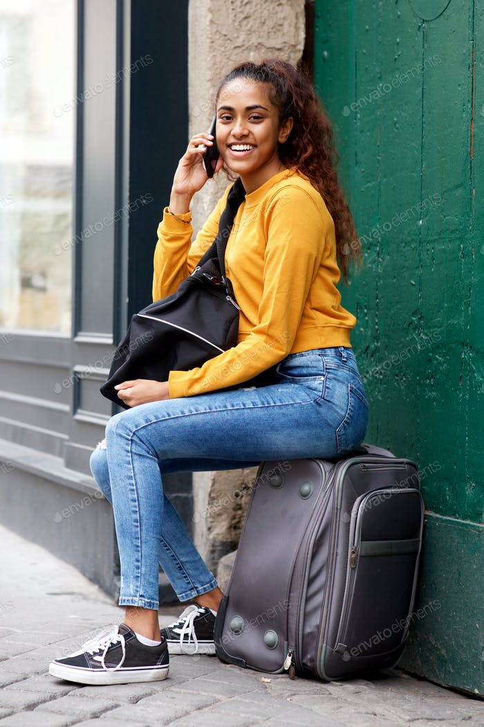 young travel woman sitting in city talking with mobile phone