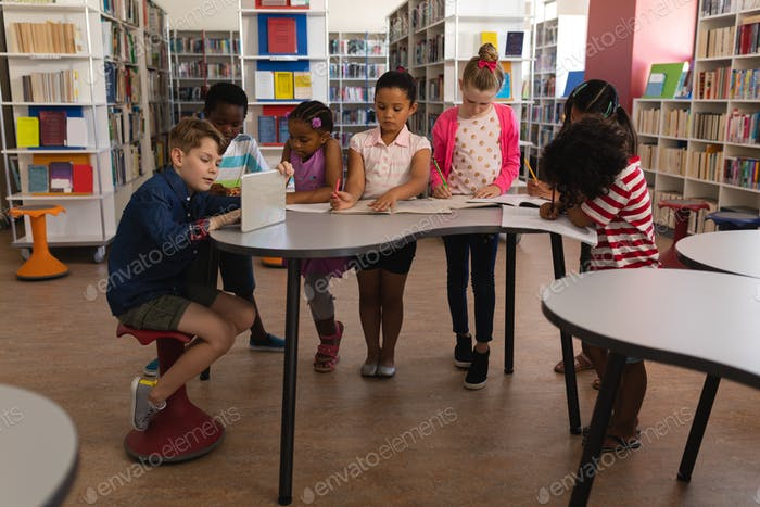 Front view of group of schoolkids studying together at table in school library