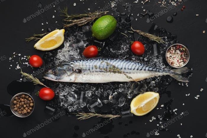 Mackerel and cooking ingredients on black background