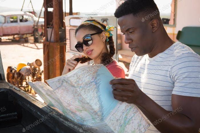 Couple looking at map in petrol pump station