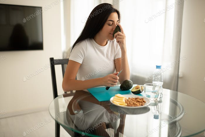 Dreamy female relishing healthy food in modern apartment