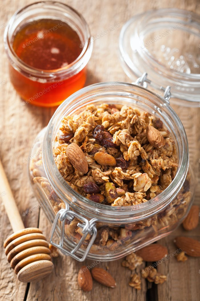 homemade healthy granola in glass jar and honey