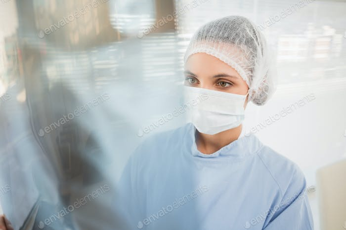 Close-up of a serious female surgeon examining blurred x-ray in the hospital
