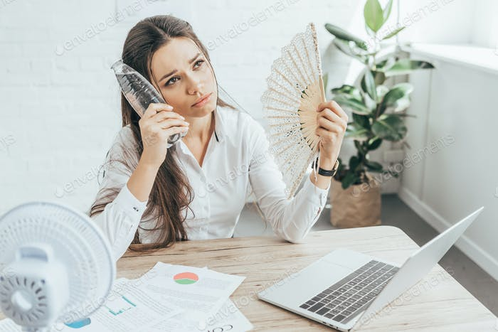 businesswoman cooling herself with electric fan, hand fan and bottle of water at workplace with