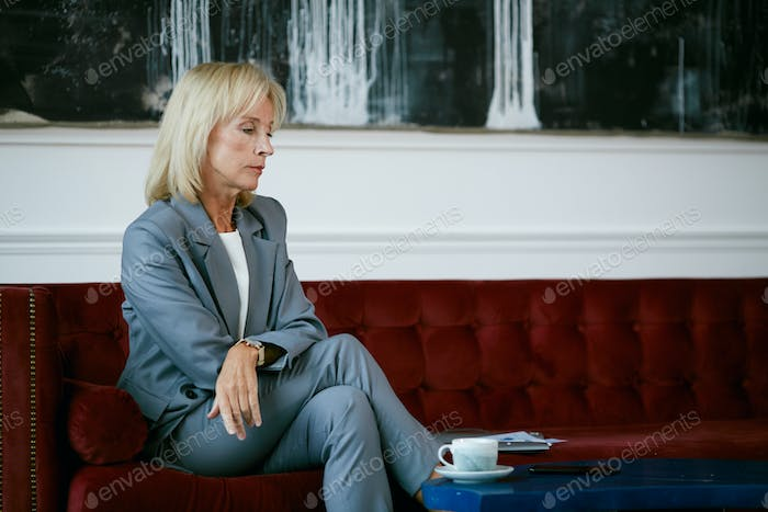 Mature Businesswoman Waiting in Cafe