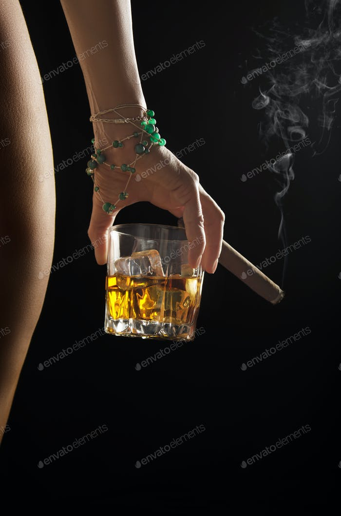 Caucasian model holds glass of whiskey with icecubes and smoking cigar in her hand